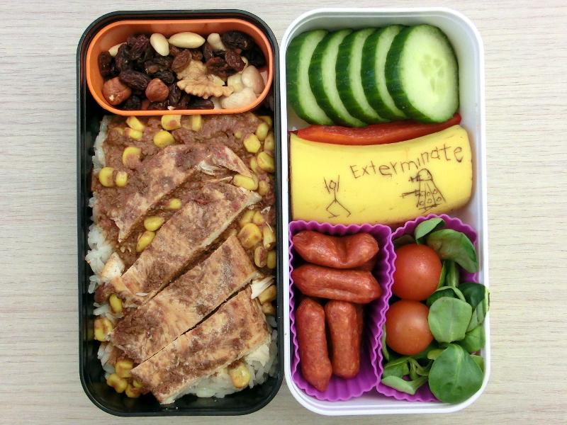 Bentobox gefüllt mit Hähnchen mit Mole, Studentenfutter, Gurke, Paprika, Banane, Cabanossi und Tomaten. Auf der Banane ist ein Dalek und das Wort Exterminate eingeritzt.