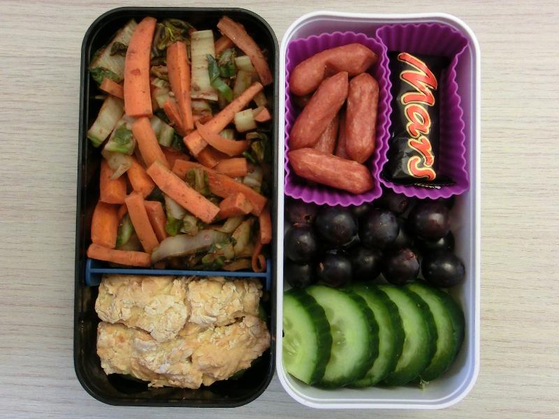 Die heutige Bentobox ist gefüllt mit Gemüsepfanne, Sodabrot-Sandwich, Cabanossi, Schokolade, Weintrauben und Gurke