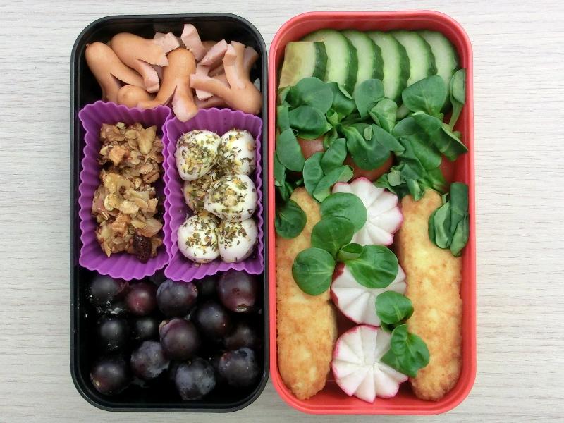 Bentobox gefüllt mit Würstchen, Müsliriegel, Mozzarella, Weintrauben, Gurke, Tomaten, Radieschen und Kartoffeltaschen