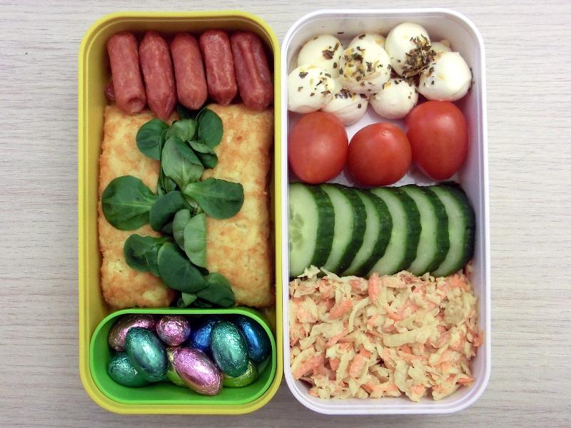 Bento-Box befüllt mit Tomaten, Gurke, Coleslaw, Mozzarella, Cabanossi, Kartoffeltaschen und Schokolade