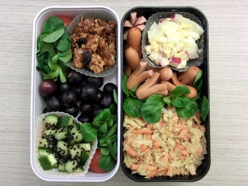 Bentobox gefüllt mit Eiersalat, Coleslaw, Würstchen, Müsliriegel, Weintrauben, Tomaten und Gurke
