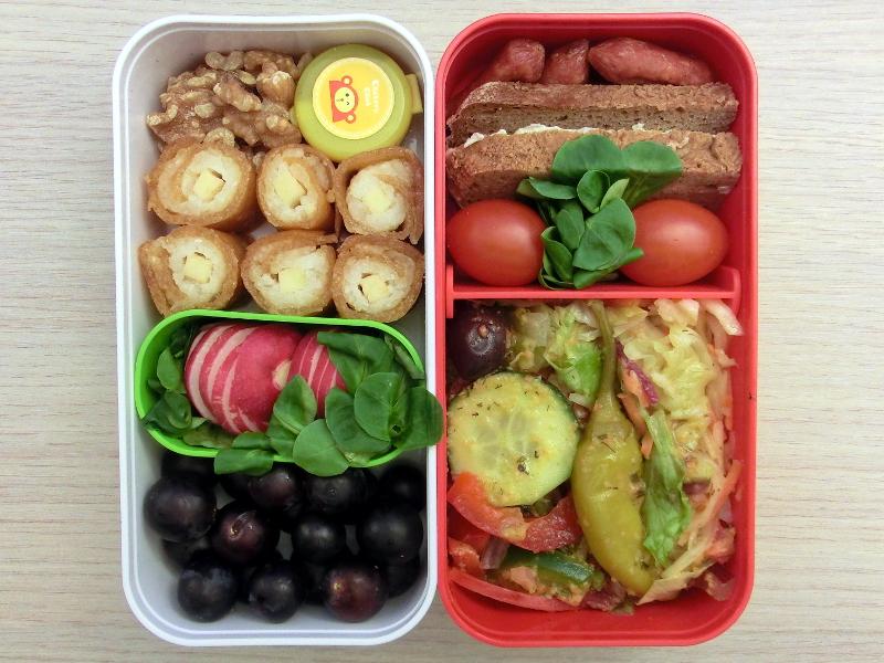 Bento gefüllt mit Salat, Tomaten, Brot, Cabanossi, Nüsse, Fruchtleder-Maki, Radieschen und Weintrauben