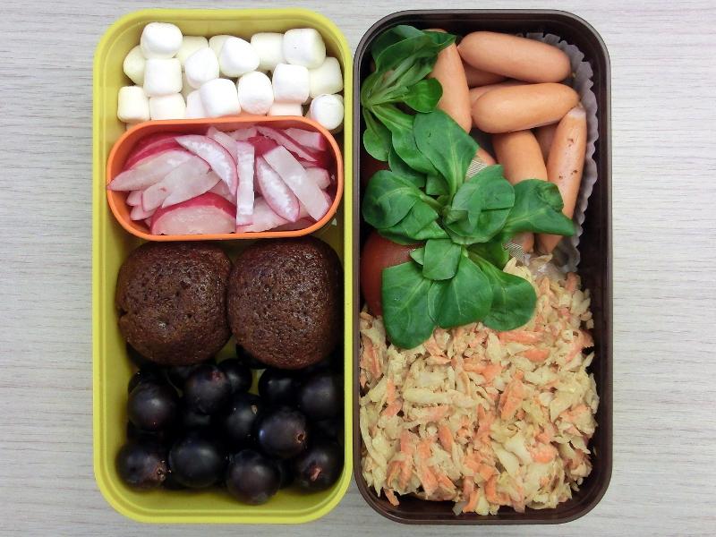 Bento gefüllt mit Coleslaw, Würstchen, Tomaten, Marshmallows, Radieschen, Schoko-Guinness-Muffins und Weintrauben