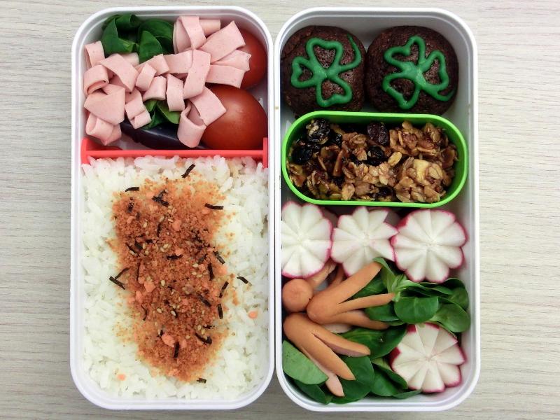 Bento gefüllt mit St. Patricks Day Muffins, Aufschnitt, Tomaten, Reis, Müsliriegel, Radieschen, Würstchen