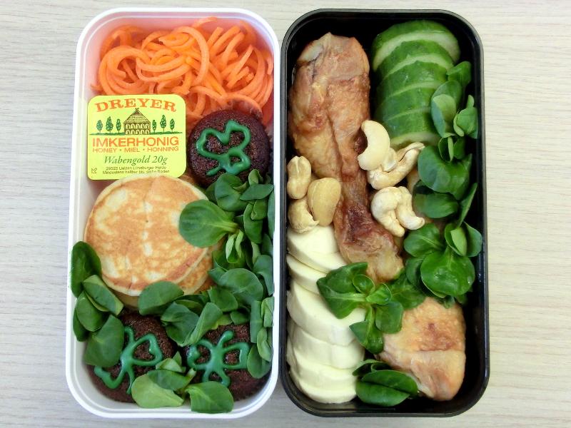 Bento gefüllt mit Pancakes mit Honig, Karotten, St. Patrick's Day Muffins, Hähnchenschenkel, Mozzarella, Gurke, Cashewnüsse und Feldsalat