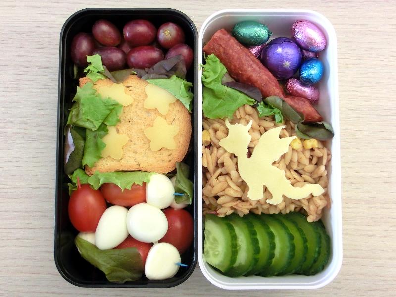Bento gefüllt mit Weintrauben, Zwieback, Tomaten-Mozzarella-Spieße, Wachteleier, Nudelpfanne, Gurke, Hartwurst, Schokolade
