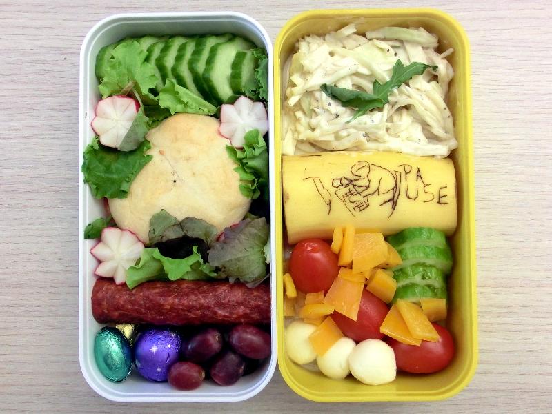Bentobox gefüllt mit Mozzarella, Tomaten, Paprika, Banane, Coleslaw, Gurke, Burger-Brötchen, Radieschen, Hartwurst, Weintrauben, Schokolade