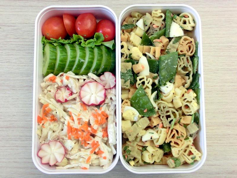 Eine Bentobox gefüllt mit Nudelsalat, Cole Slaw, Gurke, Tomaten, Radieschen