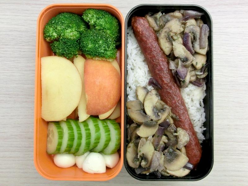 Bentobox gefüllt mit Pilzpfanne auf Reis, Hartwurst, Gurke, Apfel, Brokkoli, Mozzarella