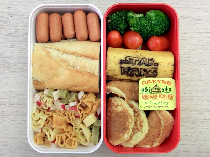 Eine Bentobox gefüllt mit Würstchen, Baguette mit Bärlauchkäse, Nudelpfanne, Brokkoli, Tomaten, Banane, Pancakes mit Honig. Auf der Banane ist das Star Wars Logo eingeritzt.