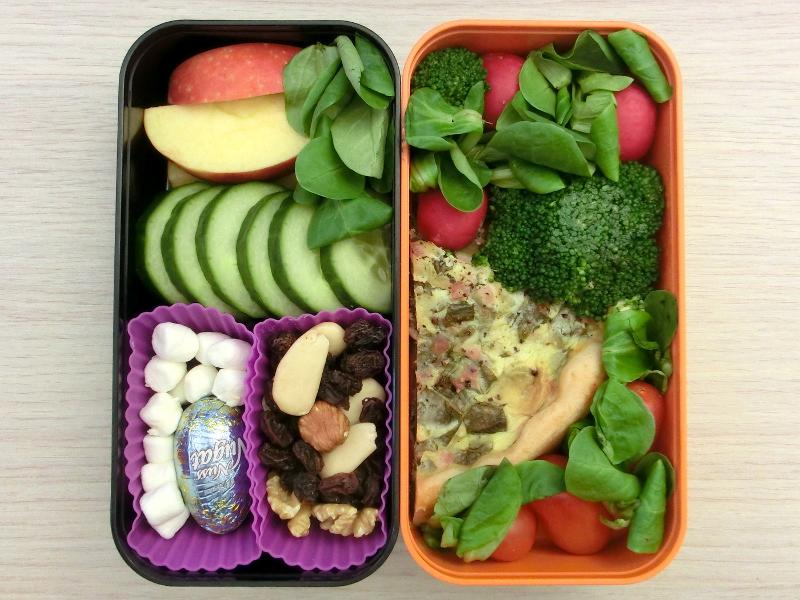 Bento Box gefüllt mit Studentenfutter, Gurke, Apfel, Radieschen, Brokkoli, Quieche, Tomate, Marshmallows, Schokolade