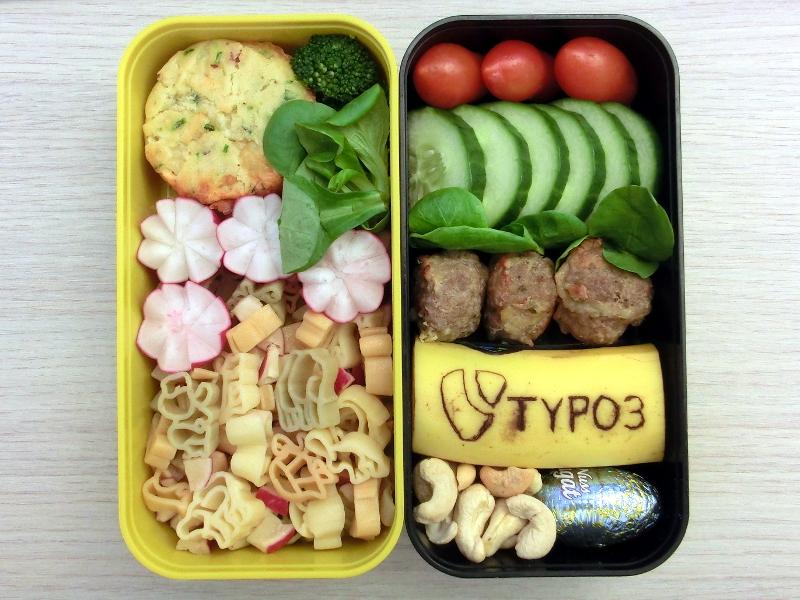 Bento Box gefüllt mit Nudelsalat, Muffin, Brokkoli, Tomaten, Gurke, Hackbällchen, Banane, Nüsse, Schokolade . Auf der Banane ist das TYPO3 Logo eingeritzt.