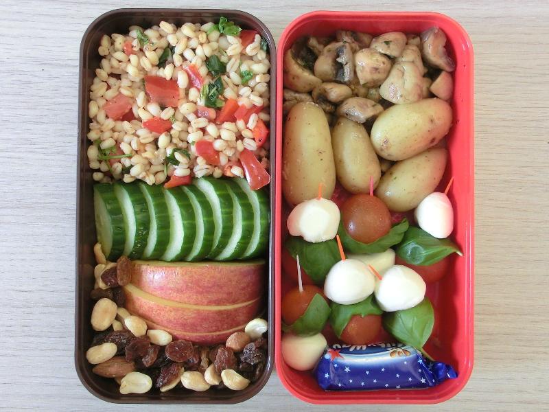 Bento Box gefüllt mit Pilze, Kartoffeln, Tomate-Mozzarella Sticks, Weichweizensalat, Gurke, Apfel, Studentenfutter