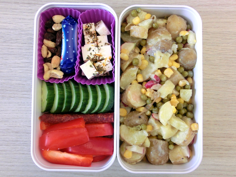 Bento Box gefüllt mit Kartoffelsalat, Schafskäse, Studentenfutter, Schokolade, Gurke, Hartwurst, Paprika
