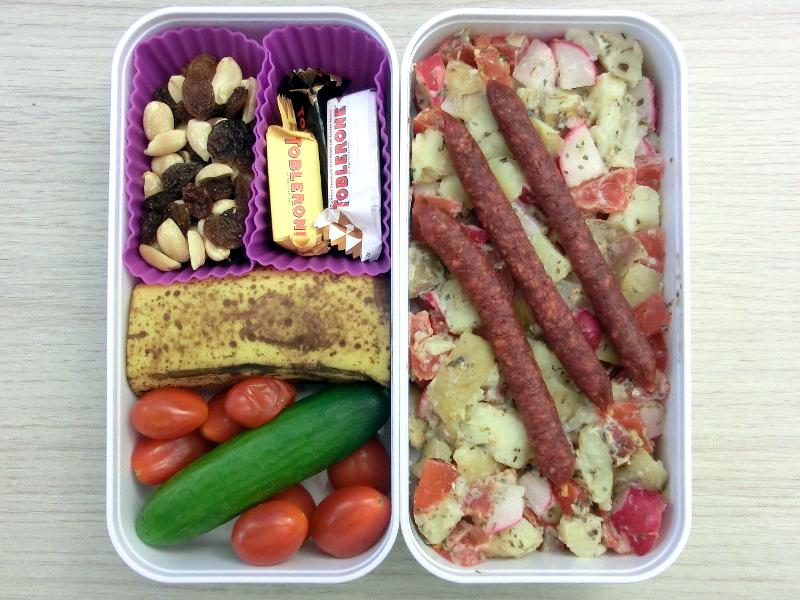 Bento Box gefüllt mit Kartoffelsalat, Würstchen, Banane, Tomaten, Studentenfutter, Toblerone