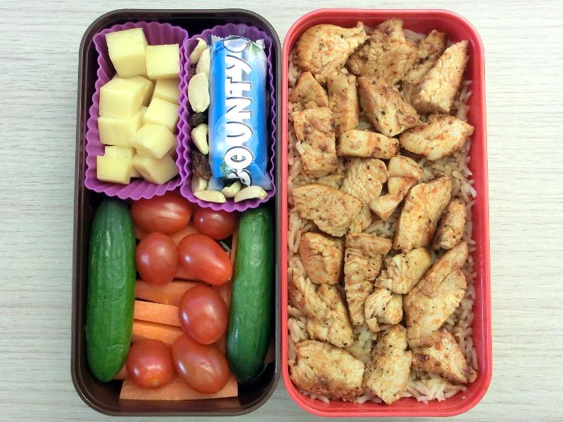 Bento Box gefüllt mit Pute, Reis, Schokolade, Käse, Gurken, Tomaten, Karotte