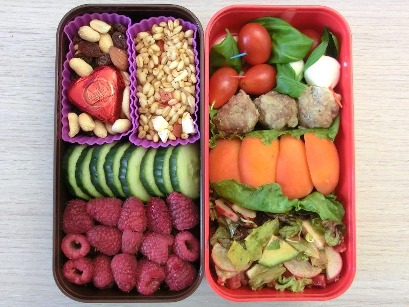 Bento Box gefüllt mit Himbeeren, Weichweizen, Studentenfutter, Schokolade, Gurke, Tomate-Mozzarella Spieße, Hackbällchen, Pfirsich, Salat