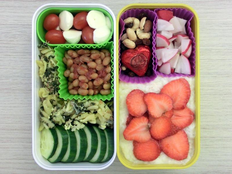 Bento Box gefüllt mit Tomaten-Morzarella, Backed Beans, Nudelauflauf, Gurke, Milchreis mit Erdbeeren, Radieschen, Studentenfutter, Schokolade