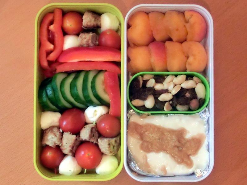 Bento Box gefüllt mit Pfirsich, Studentenfutter, Milchreis, Paprika, Tomaten-Frikadelle-Morzarella Sticks, Gurke