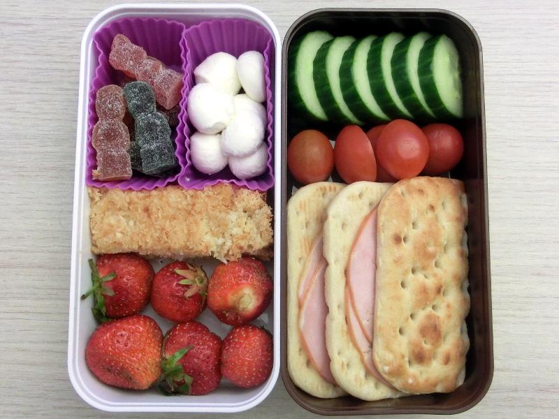 Bento Box gefüllt mit Brot mit Aufschnitt, Tomaten, Gurke, Erdbeeren, Kuchen, Weingummi, Mozzarella