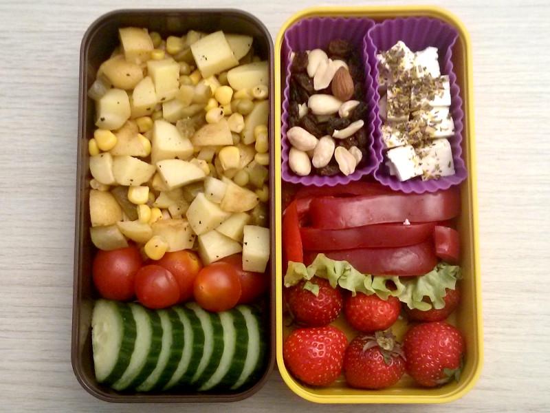 Bento Box gefüllt mit Gurke, Tomaten, Kartoffelsalat, Erdbeeren, Paprika, Studentenfutter, Schafskäse