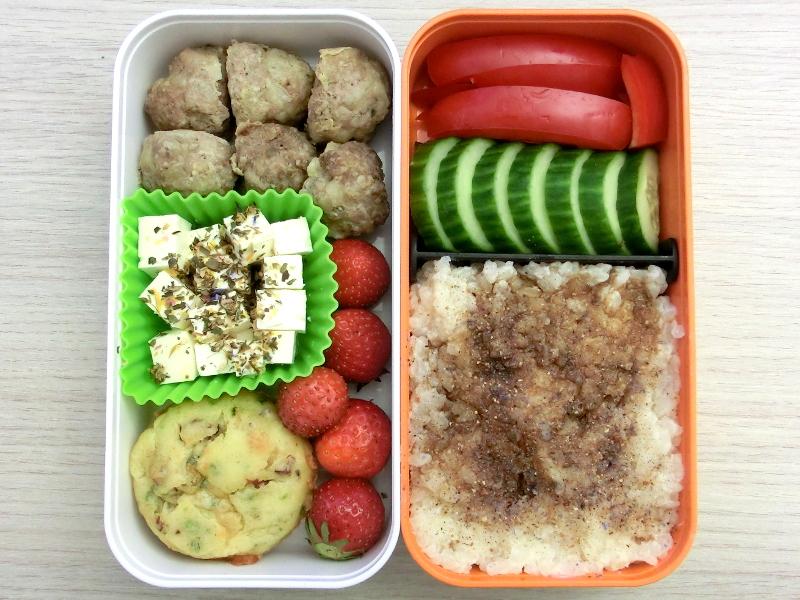 Bento Box gefüllt mit Hackbällchen, Erdbeeren, Schafskäse, Muffin, Paprika, Gurke, Milchreis