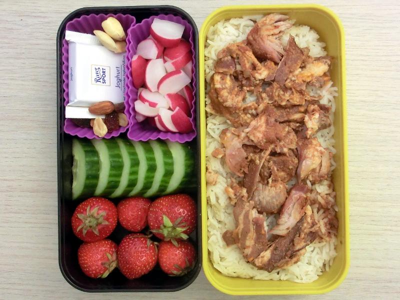 Bento Box gefüllt mit Pulled Pork, Radieschen, Studentenfutter, Schokolade, Gurke, Erdbeeren