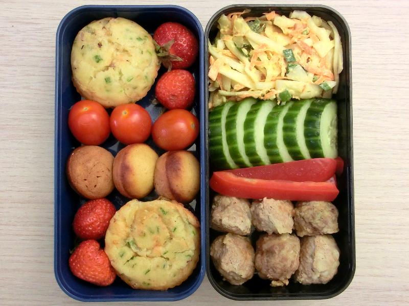 Bento Box gefüllt mit Coleslaw, Gurke, Paprika, Hackbällchen, Erdbeeren, Muffin, Tomaten