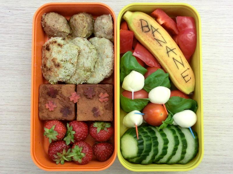 Bento Box gefüllt mit Banane, Paprika, Tomate-Mozzarella Spieße, Gurke, Hackbällchen, Gemüsebratlinge, Kuchen, Erdbeeren