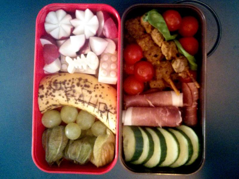 Bento Box gefüllt mit Geflügelspieße, Schinken, Tomaten, Gurke, Radieschen, Lego-Konfekt, Banane, Weintrauben, Physalis