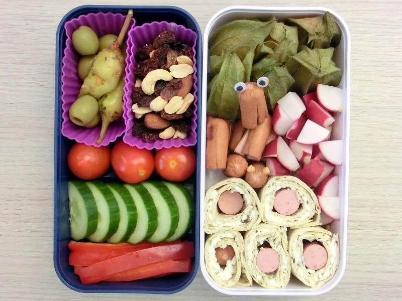 Bento Box gefüllt mit Oliven, Peperoni, Studentenfutter, Tomaten, Gurke, Paprika, Physalis, Würstchen, Radieschen, Wraps