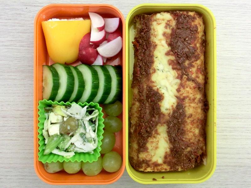 Bento Box gefüllt mit Enchilada, Radieschen, Paprika, Weintrauben, Salat, Gurke