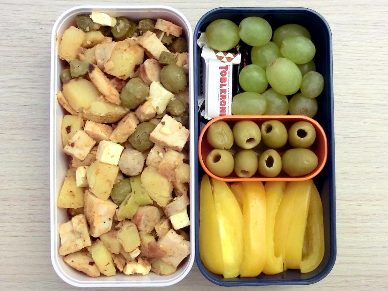 Bento Box gefüllt mit Kartoffelpfanne, Paprika, Oliven, Peperoni, Weintrauben, Toblerone