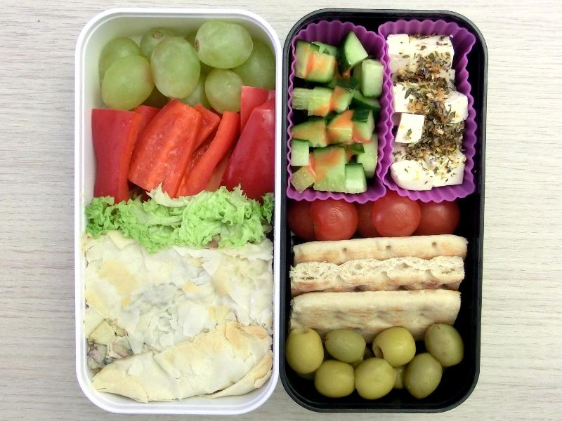 Bento Box gefüllt mit Weintrauben, Paprika, Auflauf, Gurke, Schafskäse, Tomaten, Brot, Oliven