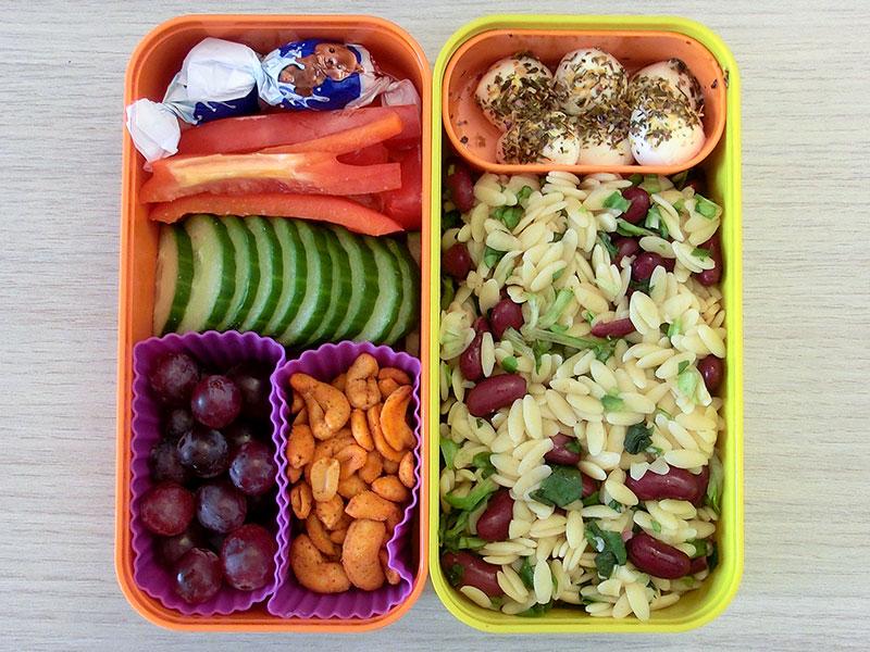 Bento Box gefüllt mit Nudelpfanne, Mozzarella, Erdnüsse, Weintrauben, Gurke, Paprika, Schokolade