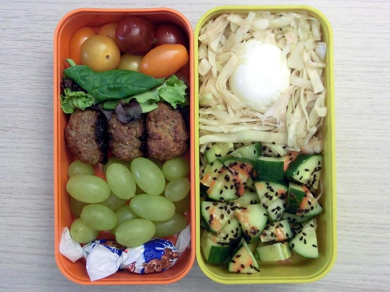 Bento Box gefüllt mit Krautsalat, Ei, Gurke, Weintrauben, Hackbällchen, Tomaten