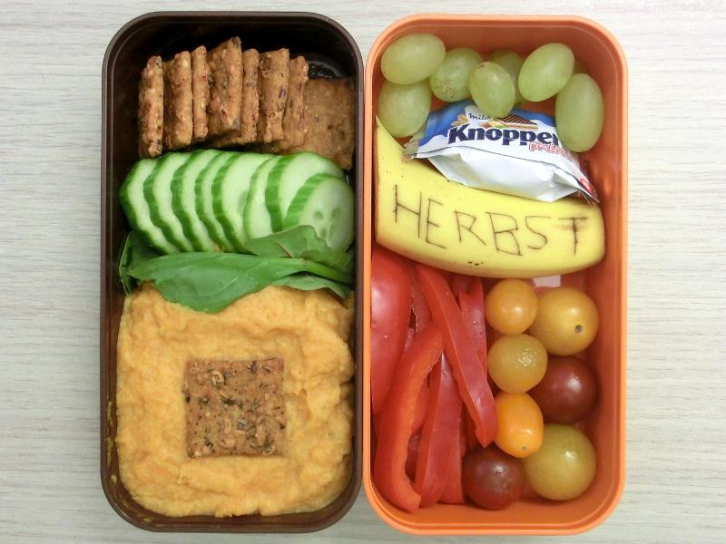Bento Box gefüllt mit Weintrauben, Banane, Tomaten, Paprika, Kracker, Gurke, Kürbismus mit Wasabi