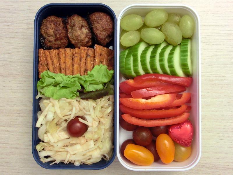 Bento Box gefüllt mit Hackbällchen, Cracker, Krautsalat, Weintrauben, Gurke, Paprika, Tomaten, Schokolade