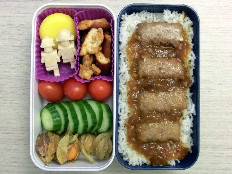 Bento Box gefüllt mit Schokolade, Babybel, Pretzels, Tomaten, Gurke, Physalis, Hackröllchen auf Reis