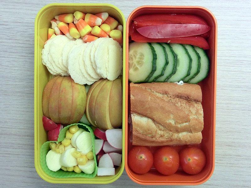 Bento Box gefüllt mit Amerikanisches Zuckerzeug, Parmesan Cracker, Apfel, Gurke, Mozzarella, Mais, Radieschen, Paprika, Baguette, Tomaten