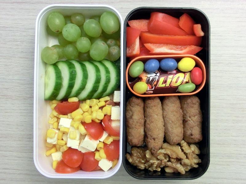 Bento Box gefüllt mit Hackröllchen, Wallnüsse, Schokolade, Paprika, Weintrauben, Gurke, Maissalat