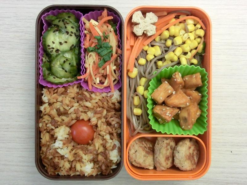Bento Box gefüllt mit Gurke, Salt, Reis, Tomaten, Frikadellen, Süßkartoffeln, Nudeln, Mais