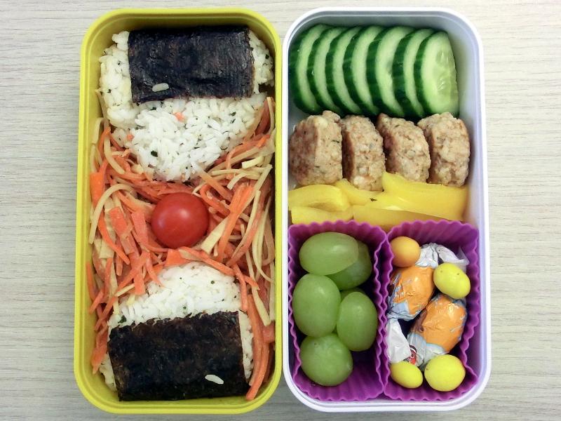Bento Box gefüllt mit Frikadellen, Gurke, Paprika, Weintrauben, Schokolade, Onigiri, Salat