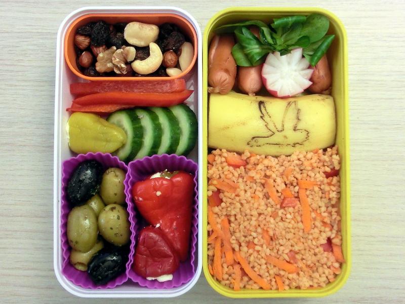 Bento Box gefüllt mit Würstchen, Radieschen, Banane, Cous Cous, Studentenfutter, Paprika, Gurke, Pepperoni, Oliven