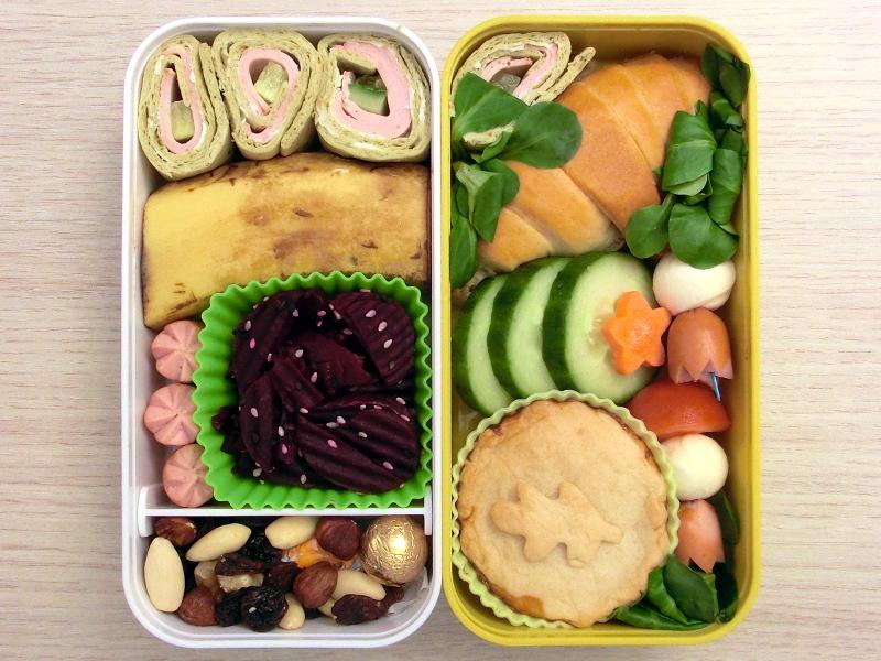 Bento Box gefüllt mit Croissant, Gurke, Wraps, Rote Beete, Banane, Würstchen, Tomaten, Mozzarella, Studentenfutter, Schokolade