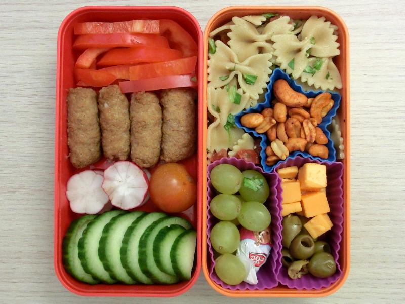 Bento Box gefüllt mit Hackröllchen, Paprika, Radieschen, Tomaten, Gurke, Nudeln, Nüsse, Weintrauben, Käse, Oliven, Schokolade