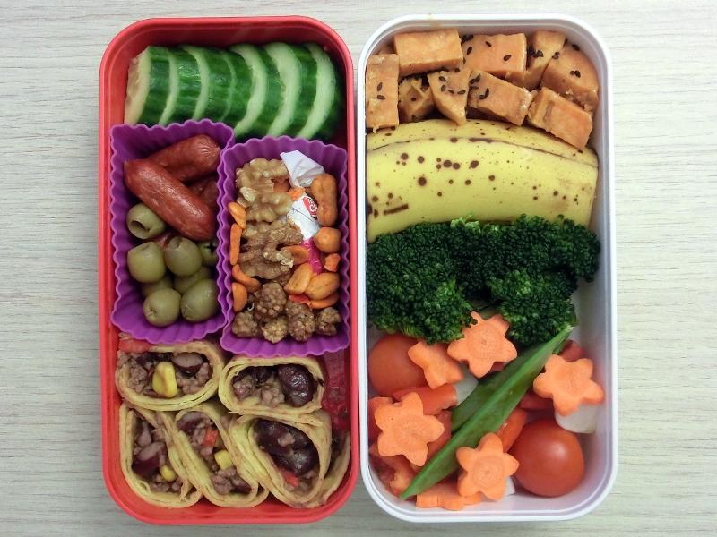 Bento Box gefüllt mit Gurke, Cabanossi, Oliven, Nüsse, Wraps mit Chilli con Carne, Süsskartoffeln, Banane, Brokkoli, Tomaten, Radieschen, Möhren