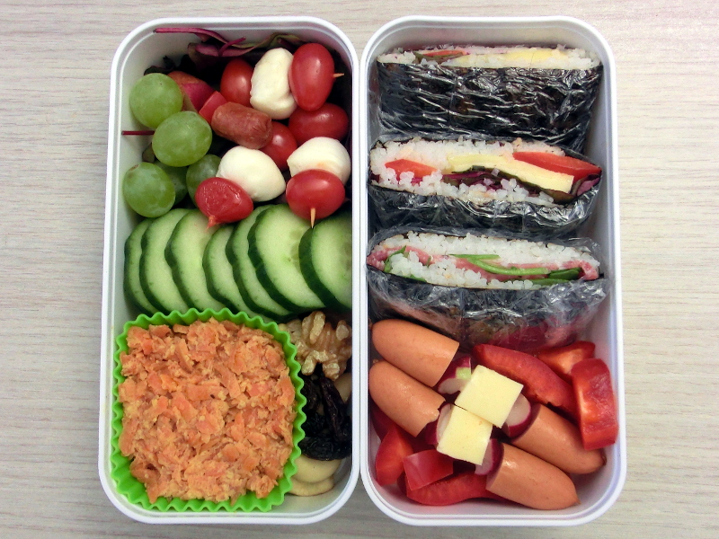 Bento Box gefüllt mit Onigirazu mit Salami, Käse und Paprika, Paprika, Würstchen, Käse, Tomaten, Mozarella, Weintrauben, Gurke, Karottensalat, Studentenfutter