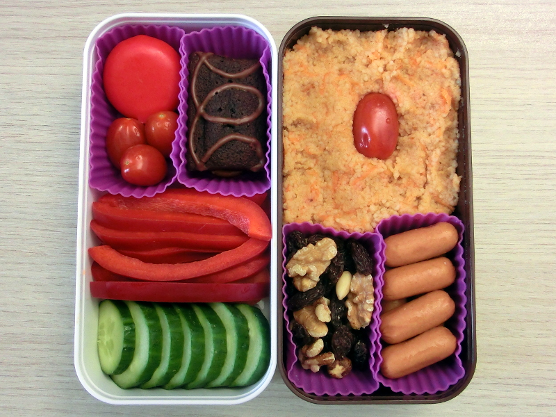 Bento Box gefüllt mit Cous Cous, Tomaten, Würstchen, Studentenfutter, Kuchen, Babybel, Paprika, Karotten, Gurke