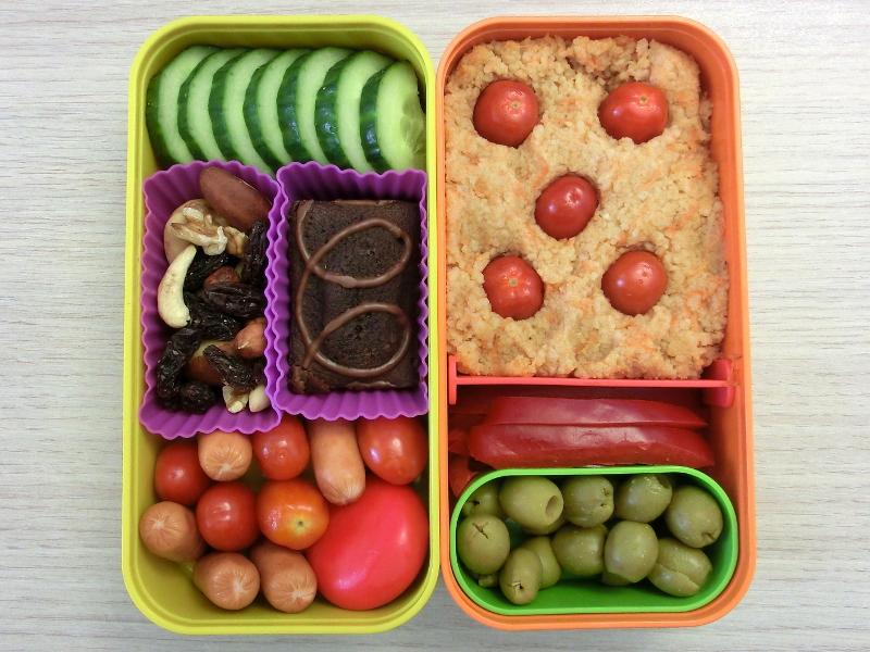 Bento Box gefüllt mit Cous Cous, Tomaten, Paprika, Oliven, Gurke, Kuchen, Studentenfutter, Würstchen, Babybel
